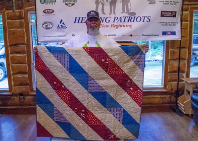 Guest and his gifted handmade quilt.