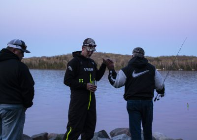 Healing Patriots Volunteer Staff fishing with a Veteran Guest on shore.